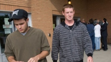James Fraser, 23, left, and brother-in-law Jeremy Rowlands leave Saskatoon, Sask. court Monday, Aug.10, 2009 following their conviction in several federal and provincial wildlife act charges. (Geoff Howe / THE CANADIAN PRESS)