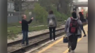 A man is seen taking photos from the train tracks in this screen grab from a video. (@CarlyAlmighty / Twitter)