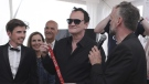 Director Quentin Tarantino poses for photographers with the Palm Dog collar award for the the dog Brandy that appeared in his film 'Once Upon a Time in Hollywood' on May 24, 2019. (Petros Giannakouris / AP)