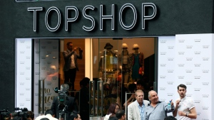 Topshop boss Philip Green, centre, points to people gathered at the opening ceremony of the first Topshop store in Hong Kong Thursday, June 6, 2013. (AP Photo/Kin Cheung)