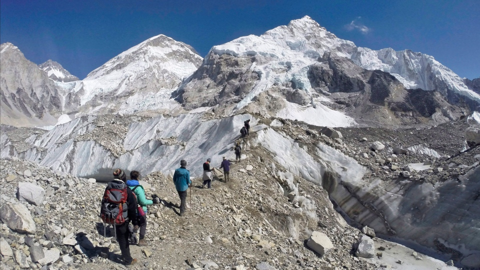 In this Monday, Feb. 22, 2016 file photo, trekkers pass through a glacier at the Mount Everest base camp, Nepal. (AP Photo/Tashi Sherpa, file)
