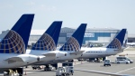 In this July 18, 2018, file photo, United Airlines commercial jets sit at a gate at Terminal C of Newark Liberty International Airport in Newark, N.J. (AP Photo/Julio Cortez, File)