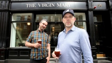 Pub co-owners Oisin Davis (L) and Vaughan Yates pose outside the Virgin Mary pub, which opened recently selling non-alcoholic drinks and is known as the 'pub with no beer', in the city centre of Dublin. (PAUL FAITH / AFP)