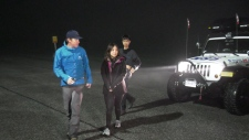 Yuhan Li (far right) with his hiking companion (middle) as they get escorted by North Shore Rescue.