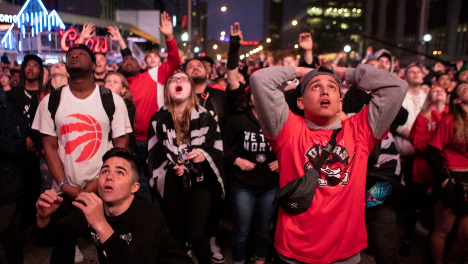 Toronto Raptors fans react as they watch game six of NBA Eastern Conference Final basketball action between the Toronto Raptors and Milwaukee Bucks on a screen outside the Scotiabank Arena, in Toronto on Saturday, May 25, 2019. (THE CANADIAN PRESS/Chris Young)