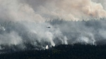 A helicopter drops a bucket of water on the Chuckegg Creek wildfire west of High Level, Alta., in a Saturday, May 25, 2019, handout photo. THE CANADIAN PRESS/Government of Alberta, Chris Schwarz, *MANDATORY CREDIT*