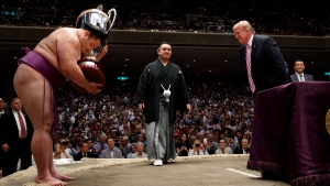 "President Donald Trump presents the ""President's Cup"" to the Tokyo Grand Sumo Tournament winner Asanoyama, at Ryogoku Kokugikan Stadium, Sunday, May 26, 2019, in Tokyo. (AP Photo/Evan Vucci)"