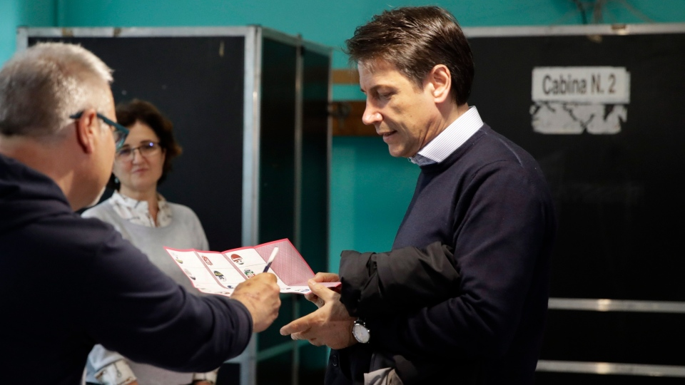 Italian Premier Giuseppe Conte is given a pencil and ballot to vote for the European Parliament elections at a polling station in Rome, Sunday, May 26, 2019. (AP Photo/Alessandra Tarantino)