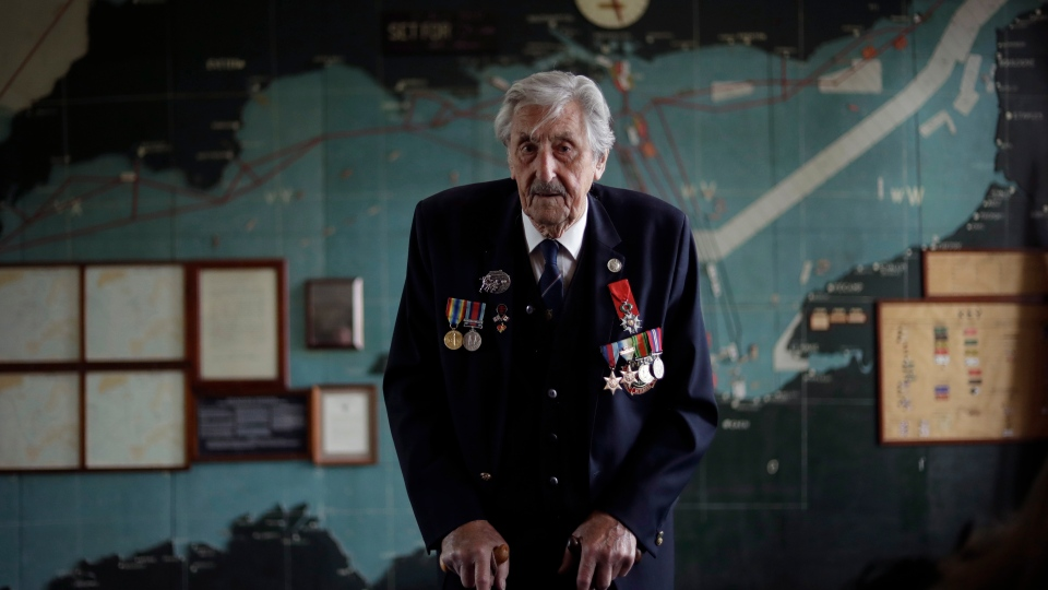 British D-Day veteran Leonard 'Ted' Emmings, who was a naval Coxswain serving on a small landing craft which landed 36 Canadians on Juno beach in France, poses for photographs backdropped by the map used to plan the Normandy D-Day landings at Southwick House near Portsmouth, England, May 9, 2019. (AP Photo/Matt Dunham)