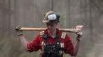 A firefighter carries an axe to battle northwest Alberta wildfires near the town of High Level on Friday, May 24, 2019. (THE CANADIAN PRESS/HO-Government of Alberta-Chris Schwarz)