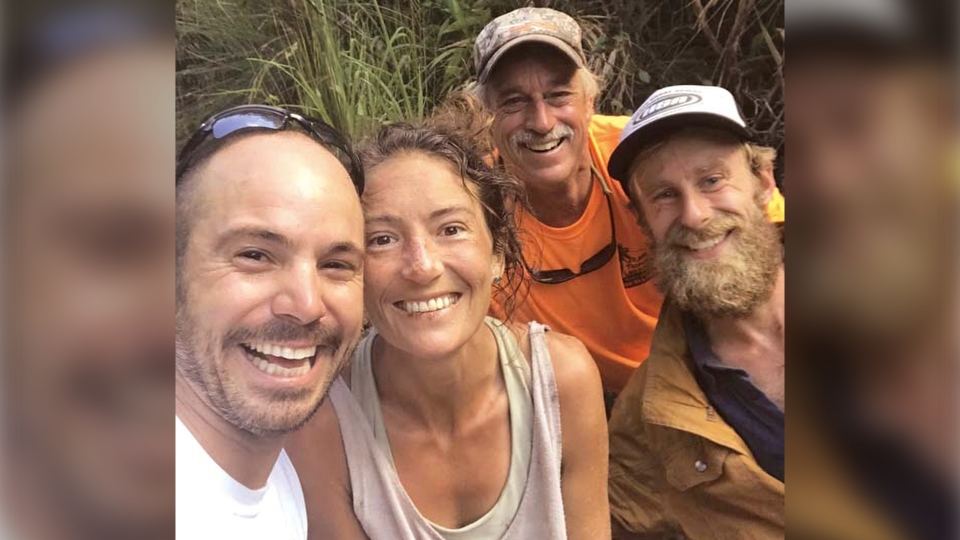 In this Friday, May 24, 2019, photo provided by Troy Jeffrey Helmer, resident Amanda Eller, second from left, poses for a photo after being found by searchers, Javier Cantellops, far left, Helmer and Chris Berquist above the Kailua reservoir in East Maui, Hawaii, on Friday afternoon. (Troy Jeffrey Helmer via AP)
