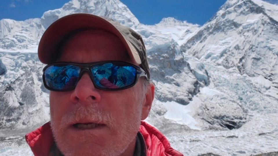 This April 2019 selfie photo provided by Mark Kulish shows his brother Christopher Kulish beneath Mount Everest. (Christopher Kulish/Mark Kulish via AP)