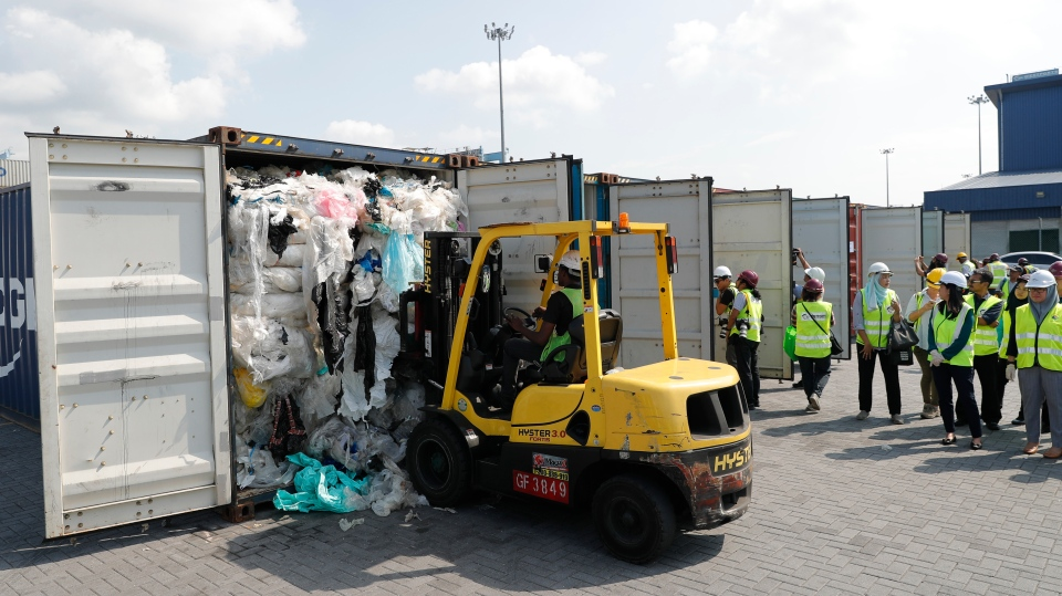 Officers from the Ministry of Environment examine a container full of non-recyclable plastic which was detained by authorities at the west port in Klang, Malaysia, Tuesday, May 28, 2019. (AP Photo/Vincent Thian)