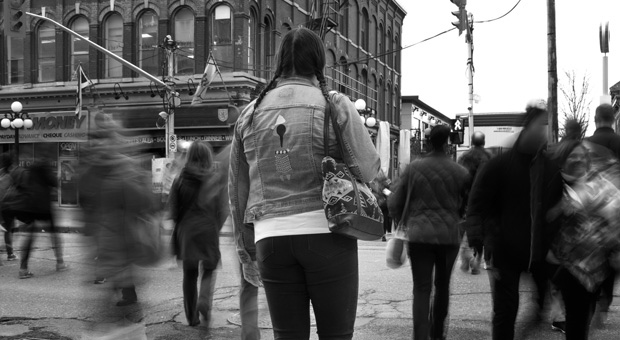 A woman stands on the sidewalk as people cross a street in this undated photo illustration. A national hotline to help victims and survivors of human trafficking is now taking calls, with the organization behind the initiative saying it hoped the service would also fill crucial gaps in public knowledge about the issue. THE CANADIAN PRESS/HO-Karen Joyner