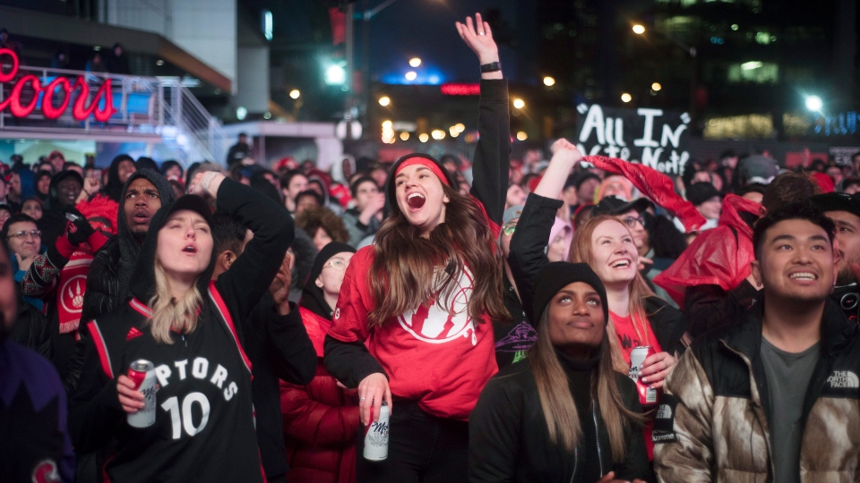 In this Sunday, May 12, 2019, file photo, basketball fans cheer for the Toronto Raptors before claiming victory over the Philadelphia 76ers outside Maple Leaf Square during the second half of an NBA Eastern Conference semifinal basketball game in Toronto. (Tijana Martin/The Canadian Press via AP, File)