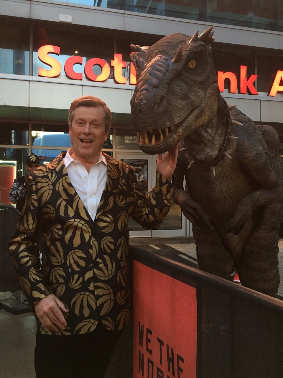 Wearing a blazer with gold Toronto Raptors logos on it, Toronto mayor John Tory poses with a man in a dinosaur costume at Jurassic Park outside Scotiabank Arena ahead of Game 1 of the NBA Eastern Conference final between Toronto and Milwaukee Bucks in Toronto on Wednesday, May 15, 2019. THE CANADIAN PRESS/HO - Twitter, @JohnTory