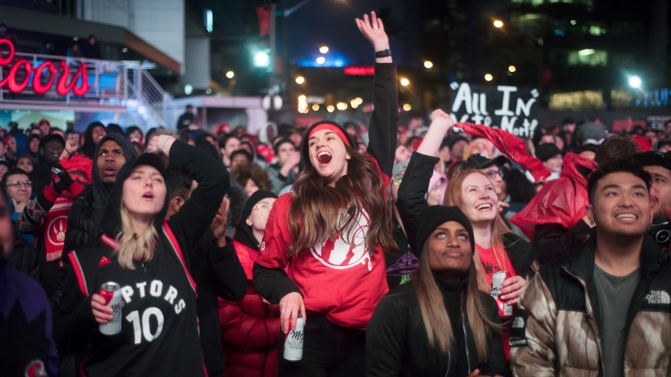 In this Sunday, May 12, 2019, file photo, basketball fans cheer for the Toronto Raptors before claiming victory over the Philadelphia 76ers outside Maple Leaf Square during the second half of an NBA Eastern Conference semifinal basketball game in Toronto.(Tijana Martin/The Canadian Press via AP, File)