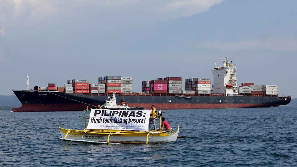 In this image released by Greenpeace, Greenpeace activists and other environmental organizations display a banner as the cargo ship MV Bavaria, the container vessel allegedly hired to ship back the 69 containers loaded with garbage from Canada, slowly enters the mouth of Subic Bay, May 30, 2019 in Subic, Zambales province west of Manila, Philippines. (Greenpeace Via AP)