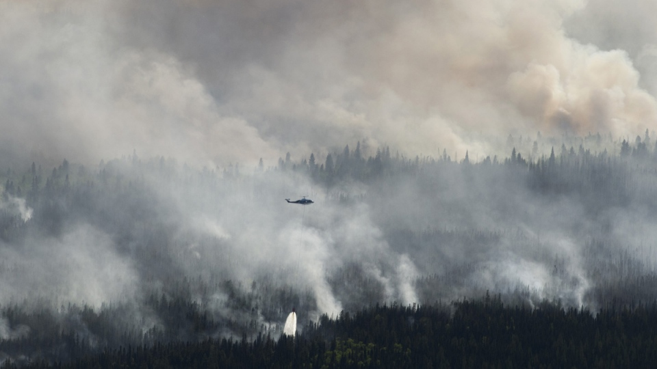 A helicopter drops a bucket of water on the Chuckegg Creek wildfire west of High Level, Alta., in a May 25, 2019 handout photo. (THE CANADIAN PRESS / Government of Alberta, Chris Schwarz)