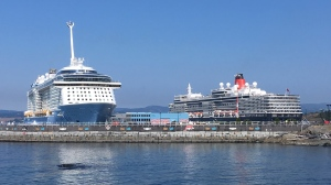 The Queen Elizabeth cruise ship (right) is docked alongside the Ovation of the Seas at Victoria's Ogden Point on Thursday, May 30, 2019. (CTV Vancouver Island)