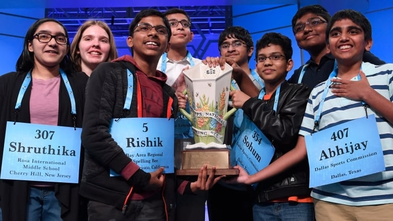 The self-described 'octo-champs' pose with the 2019 Scripps National Spelling Bee trophy. (Susan Walsh/Associated Press)
