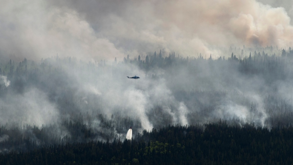 A helicopter drops a bucket of water on the Chuckegg Creek wildfire west of High Level, Alta., in a Saturday, May 25, 2019, handout photo. THE CANADIAN PRESS/Government of Alberta, Chris Schwarz,