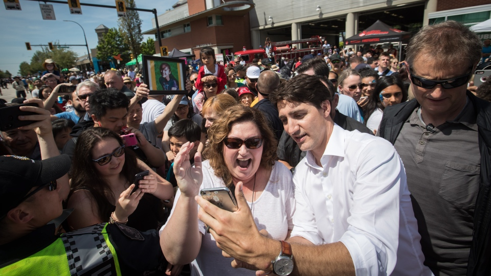 Prime Minister Justin Trudeau, front right, takes a selfie with a woman during a visit to the Hats Off Day community event in Burnaby, B.C., on Saturday June 1, 2019. THE CANADIAN PRESS/Darryl Dyck