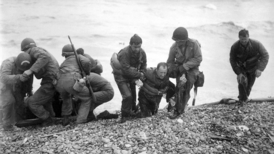 In this June 6, 1944, file photo, members of an American landing unit help their comrades ashore during the Normandy invasion. (Louis Weintraub/Pool Photo via AP, File