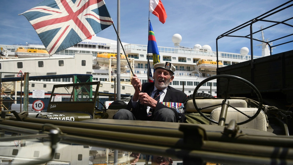 Veteran John Roberts, 95, in a jeep as he arrives to the cruise terminal to board the MV Boudicca, seen behind, ahead of its departure from the port of Dover, England, Sunday June 2, 2019. (Kirsty O'Connor/PA via AP)