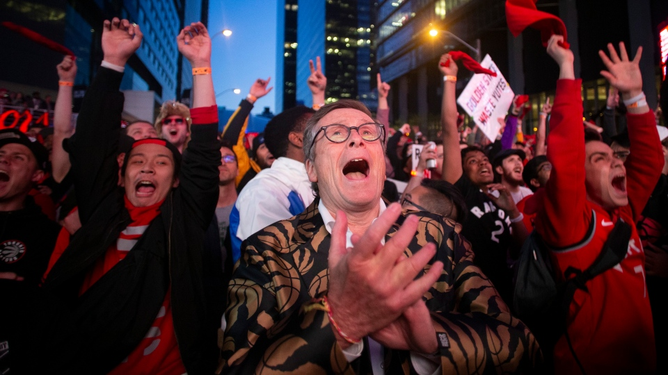 "Toronto Mayor John Tory, centre, joins Raptors fans in the fan area known as ""Jurassic Park"" outside the Scotiabank Arena as they watch Game 2 of the NBA Finals between the Toronto Raptors and Golden State Warriors in Toronto on Sunday, June 2, 2019. THE CANADIAN PRESS/Chris Young"
