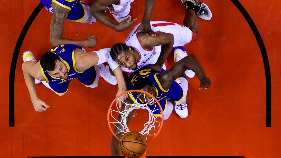 Toronto Raptors forward Kawhi Leonard, centre, eyes the ball with Golden State Warriors forward Draymond Green (23) and Golden State Warriors centre Andrew Bogut, left, during second half of Game 2 NBA Finals basketball action in Toronto on Sunday, June 2, 2019. THE CANADIAN PRESS/Nathan Denette