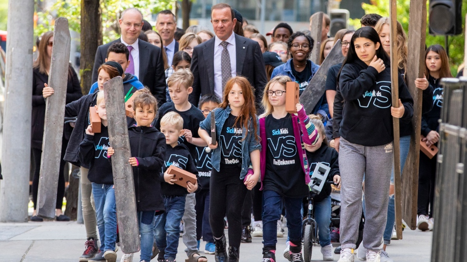 Donor Peter Gilgan, centre, joins former SickKids patients in a procession around the hospital Monday, celebrating the announcement of his $100-million gift. (Photo courtesy Carlos Osorio/SickKids Foundation)