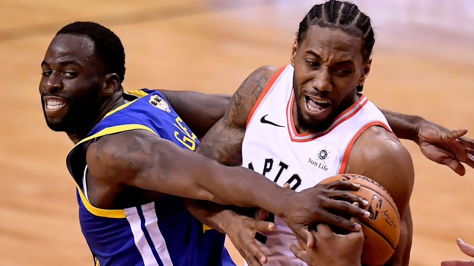 Golden State Warriors forward Draymond Green (23) tries to take the ball from Toronto Raptors forward Kawhi Leonard (2) during second half Game 2 NBA Finals action, in Toronto on Sunday, June 2, 2019. THE CANADIAN PRESS/Frank Gunn