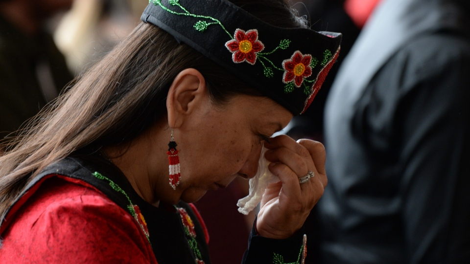 A woman shows her emotions as she listens to speakers during ceremonies marking the release of the Missing and Murdered Indigenous Women report in Gatineau, Monday June 3, 2019. (THE CANADIAN PRESS/Adrian Wyld)