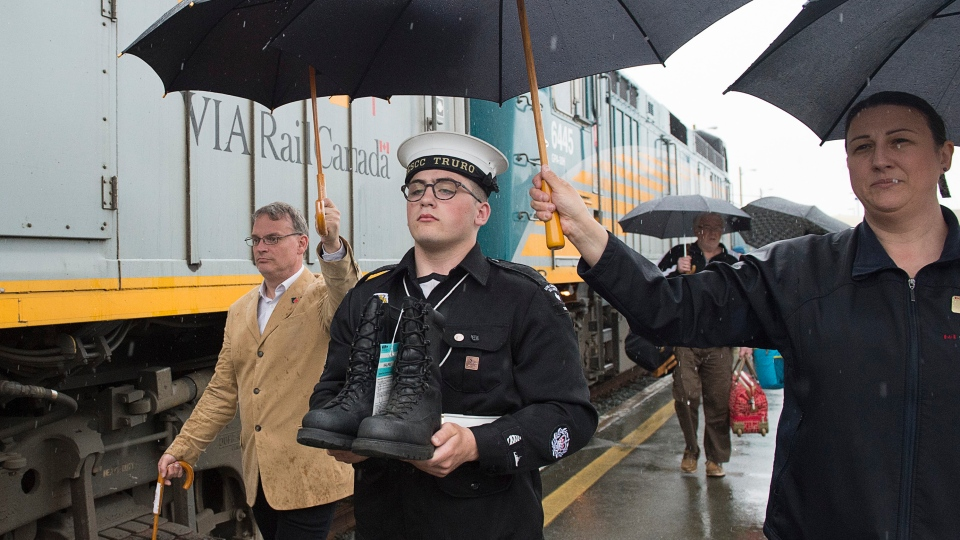 Chief Petty Officer (second class) Aaron MacCabe, a member of the Royal Canadian Sea Cadets, carries a pair of combat boots from a VIA Rail train at the end their journey from Vancouver to Halifax on Monday, June 3, 2019. (THE CANADIAN PRESS/Andrew Vaughan)