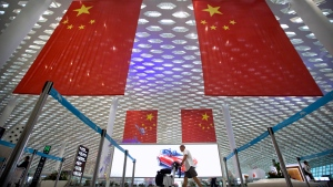 FILE - In this Oct. 10, 2018, file photo, a traveler pushes his luggage beneath large Chinese flags hanging from the ceiling in Shenzhen Bao'an International Airport in Shenzhen in southern China's Guangdong province. (AP Photo/Mark Schiefelbein, File)