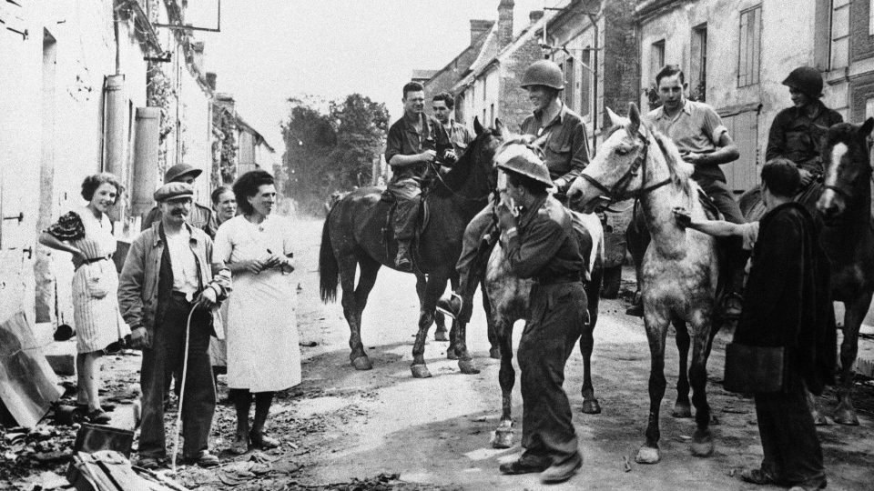 In this Aug. 30, 1944 file photo, American soldiers ride horses captured from the retreating Germans are met by town residents as they enter the French town of Chambois, Normandy, France. (AP Photo, File)