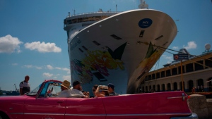 Tourists who have just disembarked from a cruise liner, tour the city aboard a vintage American convertible, in Havana, Cuba, Tuesday, June 4, 2019. (AP Photo/Ramon Espinosa)