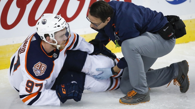 Edmonton Oilers' Connor McDavid, left, has his knee tended too after crashing into Calgary Flames goalie Mike Smith during second period NHL hockey action in Calgary, Saturday, April 6, 2019.THE CANADIAN PRESS/Jeff McIntosh