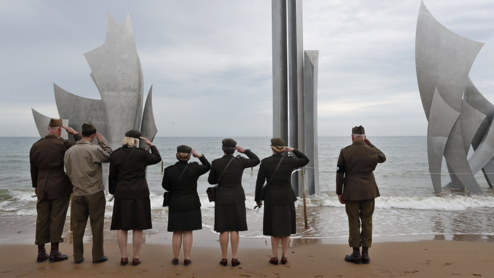 Enthusiasts of England salute in front of The Brave, a monument dedicated to the American soldiers who landed on Omaha Beach on D-Day, in Saint-Laurent-sur-Mer, Tuesday, June 4, 2019, in Normandy. (AP Photo/Thibault Camus)