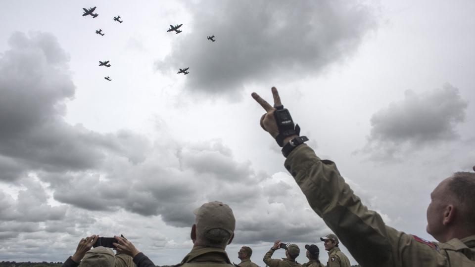 Spectators look as planes fly overhead during a group parachute jump in Carentan, Normandy, France, on June 5, 2019. (Rafael Yaghobzadeh / AP)