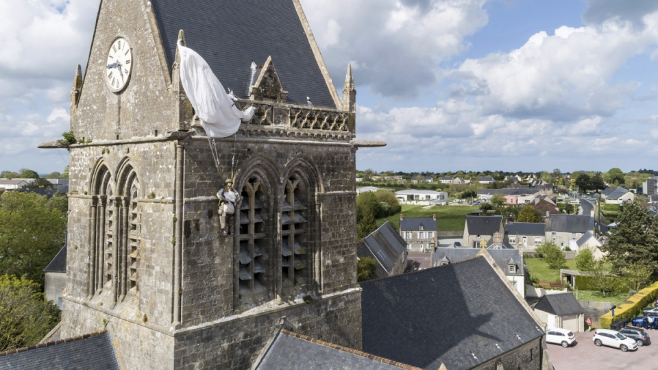 In this photo taken with a drone, a dummy paratrooper representing a Second World War paratrooper from the 82nd Airborne hangs on the bell tower of the church of Sainte Mere Eglise, in Normandy, France, on May 9, 2019. (David Vincent / AP)