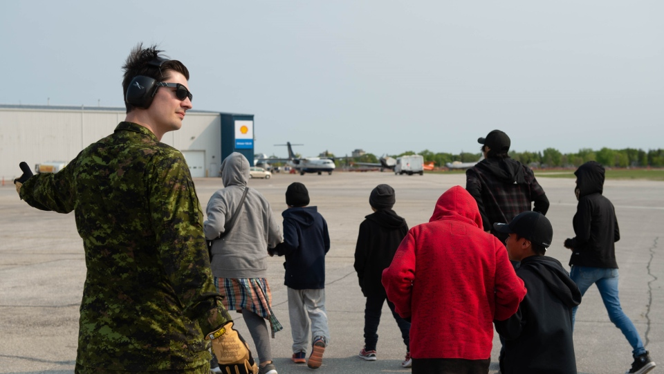 Cpl. Steven Cayen from 17 Wing Winnipeg assists evacuees from Pikangikum, Ont. who were relocated to Winnipeg because of forest fires burning in Northern Ontario, as part of Operation LENTUS on Sunday, June 2, 2019. (THE CANADIAN PRESS/HO--Cpl. Darryl Hepner, 17 Wing Imaging)