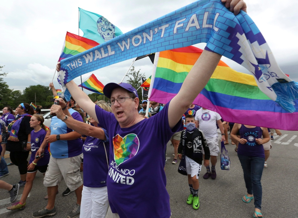 Fans march outside the stadium before the Boston Breakers played the Orlando Pride. This year's pride celebrations include many references of the Stonewall riots, marking the 50th anniversary. (Stephen M. Dowell/Orlando Sentinel via AP)