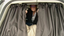 Diane Claveau draws curtains in her van.