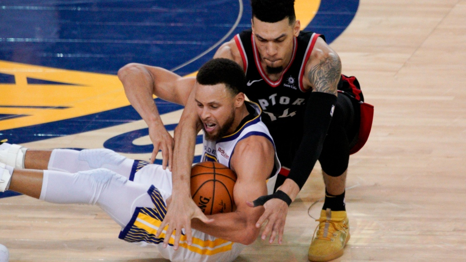 Toronto Raptors guard Danny Green, top, reaches over Golden State Warriors guard Stephen Curry during the second half of Game 3 of basketball's NBA Finals in Oakland, Calif., Wednesday, June 5, 2019. (AP Photo/Tony Avelar)
