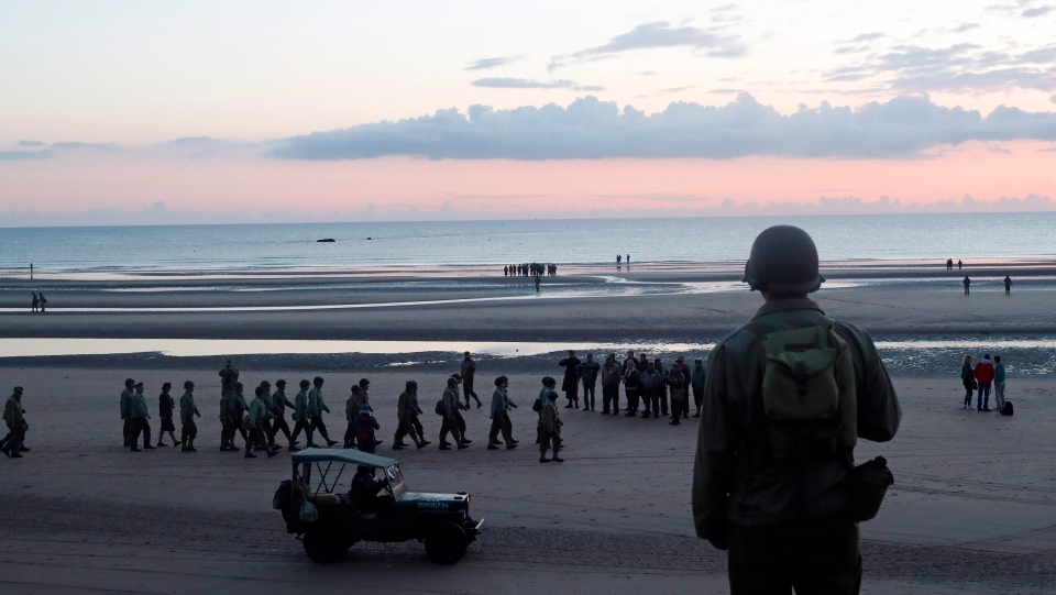 A World War II reenactor looks out over Omaha Beach, in Normandy, France, at dawn on Thursday, June 6, 2019 during commemorations of the 75th anniversary of D-Day. (AP Photo/Thibault Camus)
