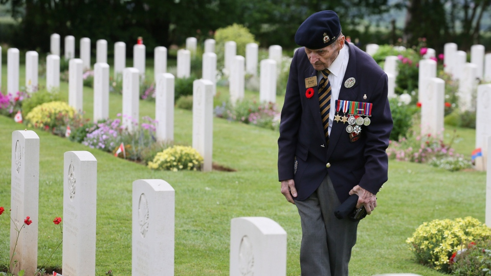 Canadian World War II veteran Bill Tymchuk, looks at headstones after attending a ceremony at the Beny-sur-Mer Canadian War Cemetery in Reviers, Normandy, France, Wednesday, June 5, 2019. (AP Photo/David Vincent)