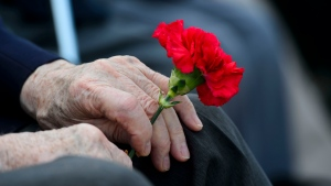 A Veteran of the Second World War holds a flower as he visits Juno Beach while taking part in the D-Day 75th Anniversary Canadian National Commemorative Ceremony at Juno Beach in Courseulles-Sur-Mer, France on Thursday, June 6, 2019. THE CANADIAN PRESS/Sean Kilpatrick