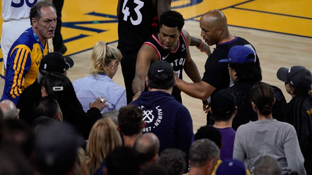 Toronto Raptors guard Kyle Lowry, middle, gestures next to referee Marc Davis (8) near the front row of fans during the second half of Game 3 of basketball's NBA Finals between the Golden State Warriors and the Raptors in Oakland, Calif., Wednesday, June 5, 2019.(AP Photo/Tony Avelar)